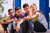 Youth culture young people group of male friends multi-ethnic teens outdoor teenagers together in park. Boys comforting sad friend kids helping depressed boy. Adolescence bond relationship poster