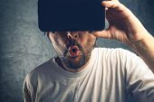 Man watching 3d pornographic content using virtual reality goggles poster