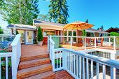 House exterior. Cozy screened walkout deck with patio area and white railings staircase. poster
