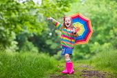 Little girl playing in rainy summer park. Child with rainbow umbrella waterproof coat and boots jumping in puddle in the rain. Kid walking in autumn shower. Outdoor fun by any weather poster