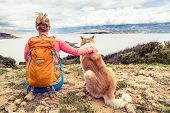 Woman hiker looking at sea with akita inu dog on seaside trail. Recreation and healthy lifestyle outdoors in summer mountains and sea nature. Beautiful inspirational landscape trekking and activity. poster