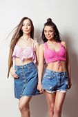 Two beautiful young women in pink crochet crop tops and denim shorts and skirt. Portrait of two modern female models holding hands and posing. Studio lighting, medium retouch, no filter. poster