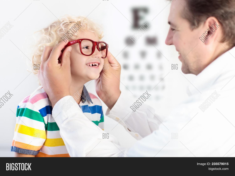 33d00cb581 Child At Eye Sight Test. Little Kid Selecting Glasses At Optician Store. Eyesight  Measurement