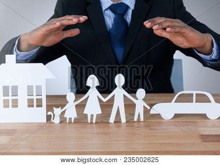 Models hands protecting house family and car cut outs