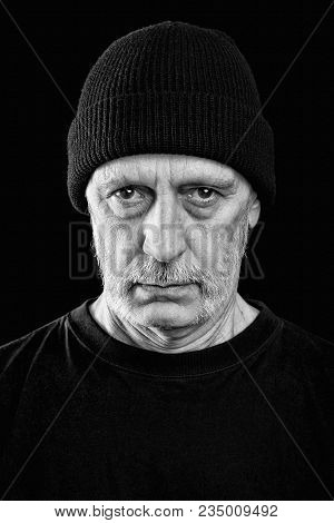 Dramatic Black And White Photo Of A Man With A Beard And A Woolen Cap
