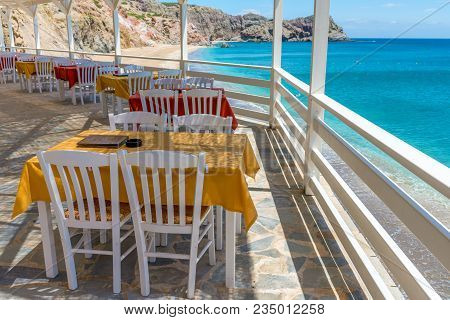 Tables And Chairs In Typical Greek Tavern Overlooking The Aegean Sea. Milso Island, Greece