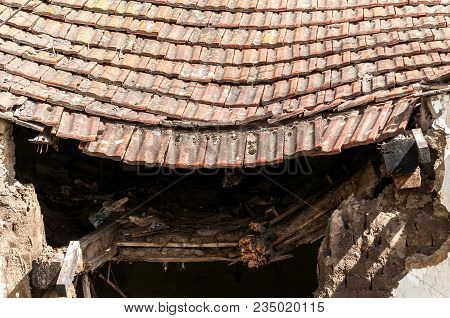 Damaged Roof. Old Abandoned House Collapsed Roof With Damaged Vintage Tiles After Natural Disaster O