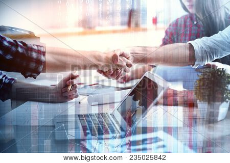 Businesspeople Shaking Hands Above Office Desktop With Laptop And Supplies. Partnership Concept. Dou