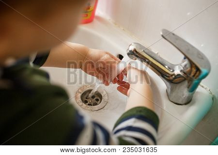 Child Washing Hands In A White Basin With Soap.
