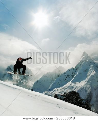 Snowboarder Jumping Indy Grab At Rocky Mountain Background And Sunny Sky. Young Man In Extreme Freer