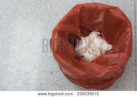 A Red Bin For Garbage With Used Surgical Gloves In The Bin