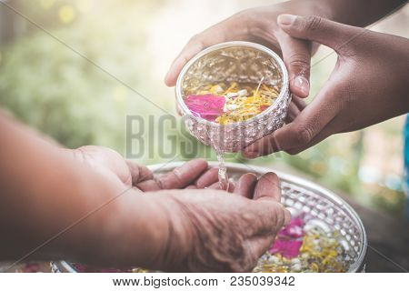 Boy Holding Bowl Of Water And Flower Pour Down To Old Hand, Respect Concept , Songkran Festival In T