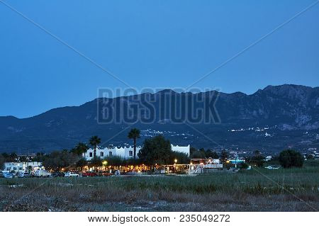 Taverns On The Street Of A Coastal Town In The Evening On The Greek Island Of Kos