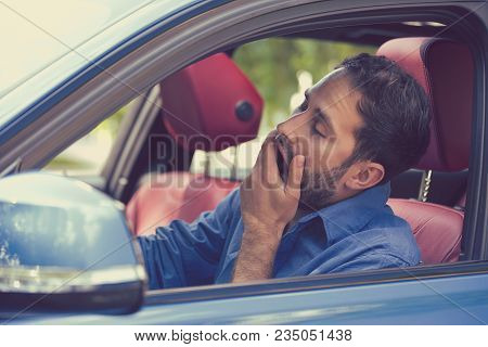 Sleepy Fatigued Yawning Exhausted Young Man Driving His Car In Traffic After Long Hour Drive. Transp