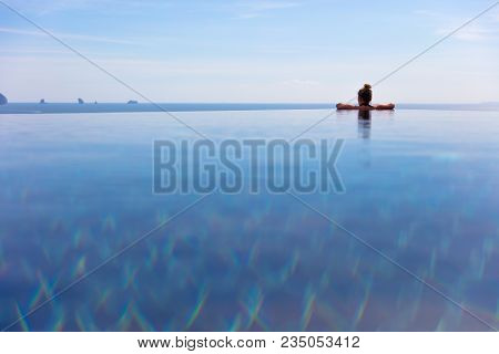 Rear View Of Woman Resting In Infinity Pool At A Aonang Beach Resort Thailand Asia
