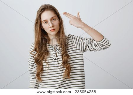 I Would Rather Kill Myself. Portrait Of Bored And Fed Up Young Woman In Glasses Making Gun Gesture A