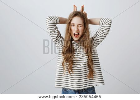 Indoor Portrait Of Good-looking Young European Woman Winking, Holding Fingers Behind Head As If Mimi