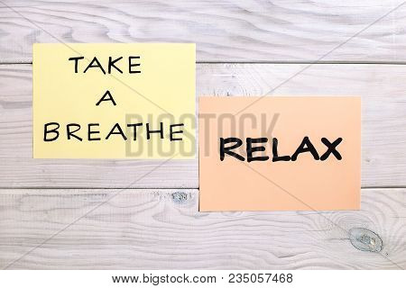 Text Take A Breath And Relax On Wooden Table.