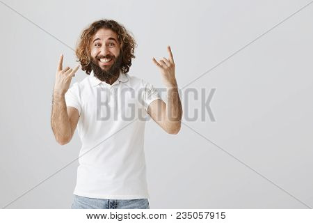 Feeling Like Rockstar. Portrait Of Upbeat Positive Eastern Guy With Beard And Curly Hair Showing Roc