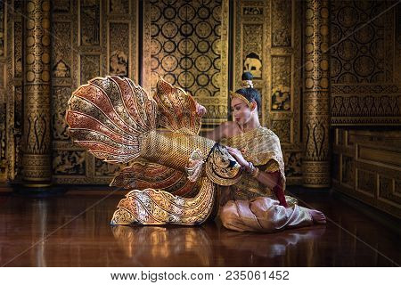 Beautiful Women In Tradition Antique Thai Pattern Dress Sit Near Gold Fish  Statuary.