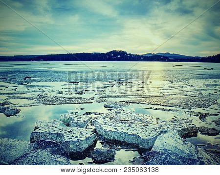 Melting Of Glaciers On Stony Shore. Fading Ice Floes, Debris After The Collapse Of A Large Glacier.