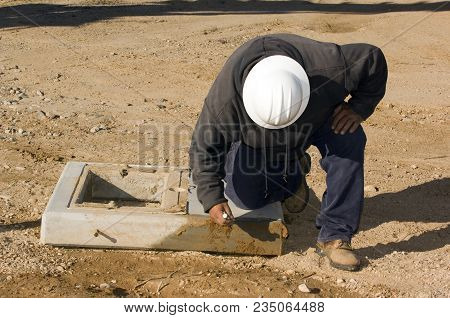 Taken In 2010. A Utility Workman Inspecting A Concrete Pad Used To Support High Voltage Transformers