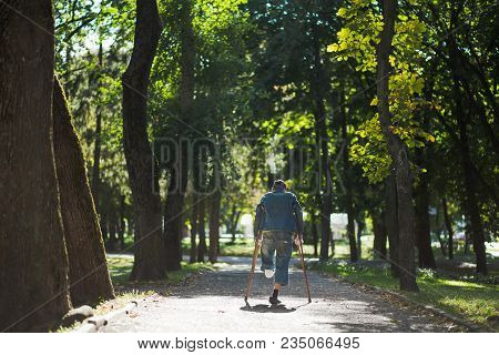 Disabled Homeless Man Without One Leg Walks In City Park Alone. Man With Amputated Leg Uses Two Wood