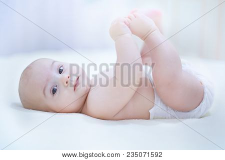 Cute Baby Infant Boy Wearing Diaper Playing With His Feet In Bed In  A Sunny Bedroom. Infant Nappy C