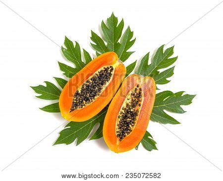 Top View Close Up Of Half Ripe Papaya Fruits On Green Leaf Isolated On White Background