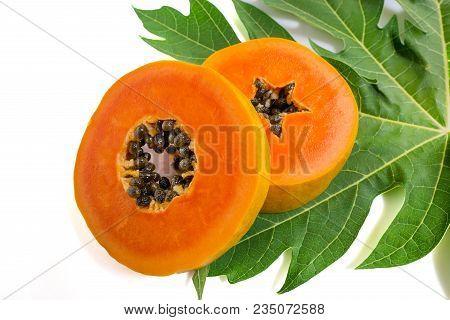 Close Up Of Slice Ripe Papaya Fruits On Green Leaf Isolated On White Background