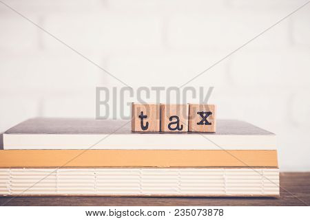 The Word Tax, Alphabet On Wooden Rubber Stamps On Top Of Books And Table. Bricks Background, Blank C