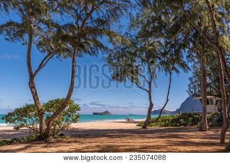 View Of Rabbit Island From Waimanalo Beach On Oahu, Hawaii With Ironwood Trees, A Lifeguard Tower An