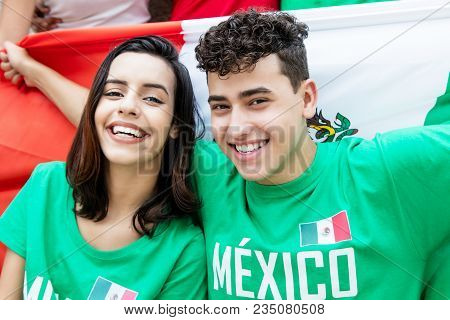 Soccer Fans From Mexico With Mexican Flag Looking At Camera Outdoors At Stadium
