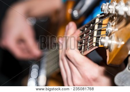 Hands And Fingers Of The Guitarist's Bass On The Fretboard