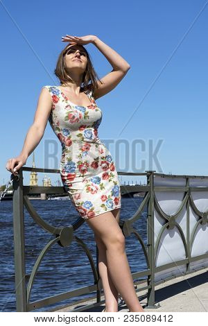 Girl In Short Dress On One Of The Blue Sky And The Neva River, Portrait Of A Young Woman