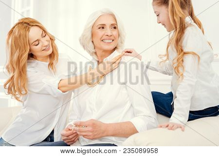 This Style Suits You Very Well. Cheerful Ladies Wearing Matching Attire Sitting On A Sofa And Grinni