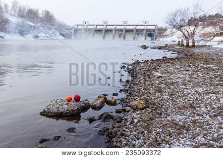 On The Bank Of The Winter River, An Orange And An Apple In The Background A Dam Over The Discharge O