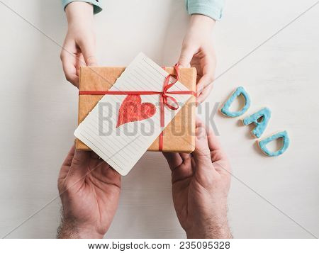 Beautiful Box With A Gift, A Card With A Heart And A Word Dad In The Hands Of A Youngest Daughter On