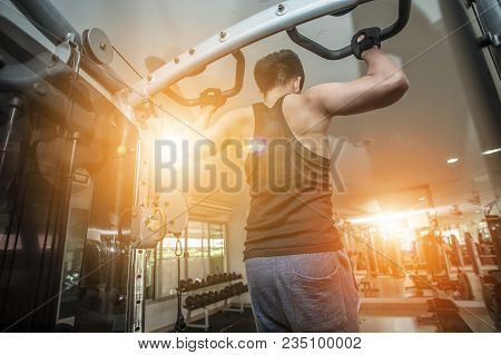 Muscular Young Man Exercising In Gym - Bodybuilder Doing Heavy Weight Exercise For Back.
