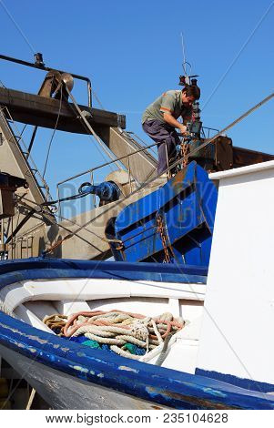 Caleta De Valez, Spain - October 27, 2008 - Man Working On A Fishing Trawler Moored In The Harbour,