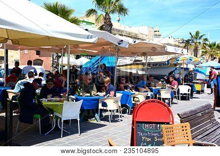 Marsaxlokk, Malta - April 1, 2017 - Tourists Relaxing At A Pavement Cafes Along The Waterfront, Mars