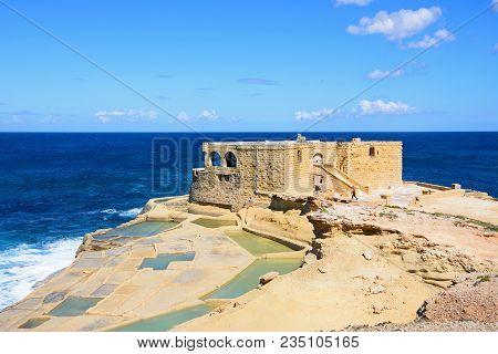 Marsalforn, Gozo, Malta - April 3, 2017 - Salt Pans Along The Waterfront With The Il-qolla I-badja B