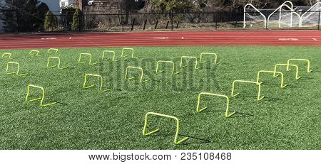 Front View Of Yellow Mini Banana Hurdles Set Up For Speed Work During Track And Field Practice At A