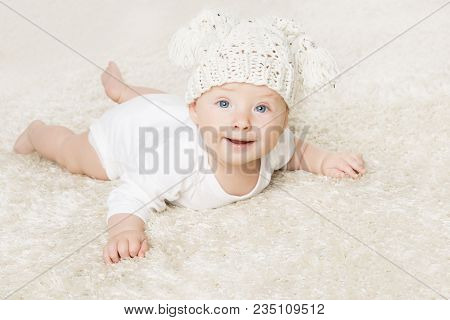 Happy Baby In White Knitted Hat Crawling On White Blanket, Infant Kid Boy Portrait, Smiling Child Si