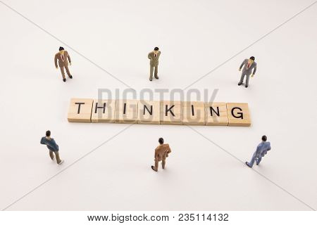 Miniature Figures Businessman : Meeting On Thinking Word By Wooden Block Word On White Paper Backgro