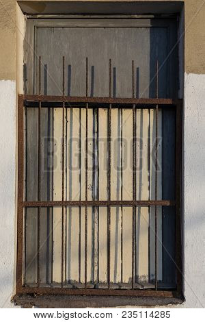 The Facade Of The Old House, Half Yellow, Half White, With A Window Grill