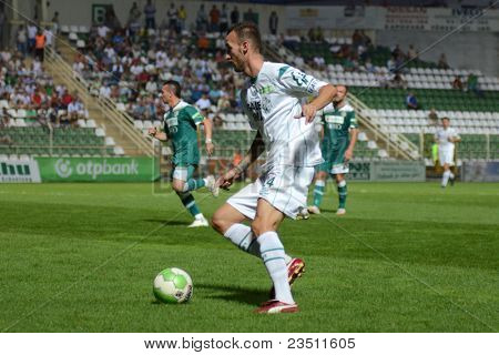 KAPOSVAR, HUNGARY - SEPTEMBER 10: David Hegedus (in white) in action at a Hungarian National Championship soccer game - Kaposvar (white) vs Gyor (green) on September 10, 2011 in Kaposvar, Hungary.