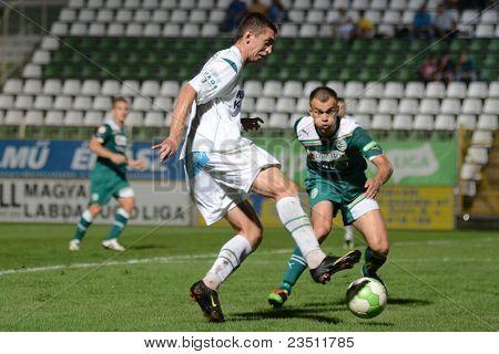 KAPOSVAR, HUNGARY - SEPTEMBER 10: Serghei Alexeev (in white) iin action at a Hungarian National Championship soccer game - Kaposvar (white) vs Gyor (green) on September 10, 2011 in Kaposvar, Hungary.