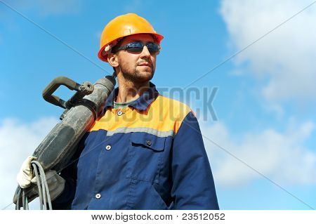 Portarait of positive Builder worker with pneumatic hammer drill equipment over blue sky poster