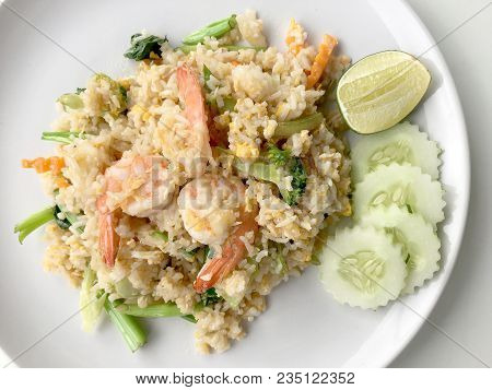 Fried Rice With Prawn Herbs And Vegetables Served With Lemon And Cucumber In White Plate On White Ba